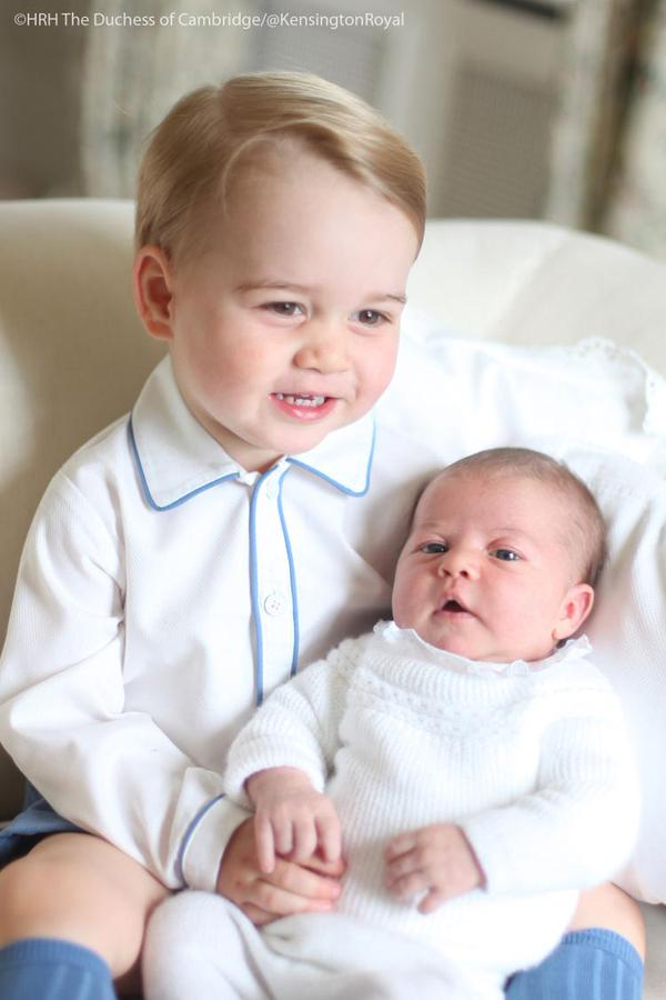 Prince George smiling and holding Princess Charlotte taken by Kate Middleton