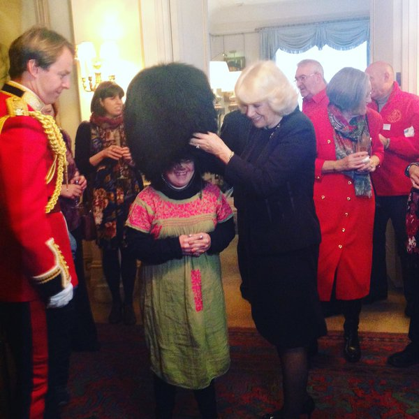 Camilla with kids trying on Welsh Gaurds hat
